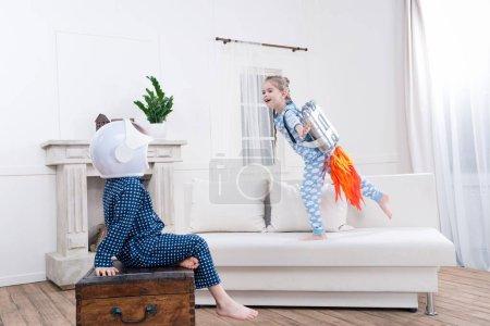 Photo pour Vue latérale de garçon et fille jouant cosmonautes à la maison - image libre de droit