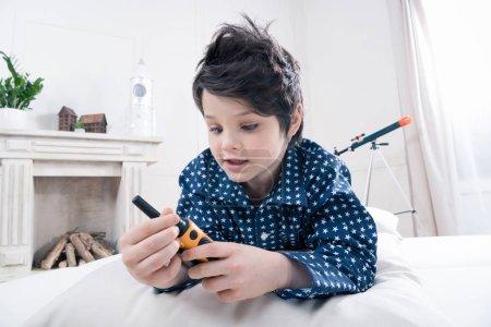 Photo pour Mignon petit garçon en pyjama tenant talkie-walkie couché sur le lit - image libre de droit