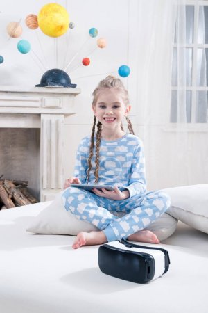 Photo for Smiling little girl in pajamas using digital tablet on bed - Royalty Free Image