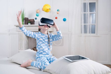 Foto de Smiling little girl in pajamas playing in virtual reality headset - Imagen libre de derechos