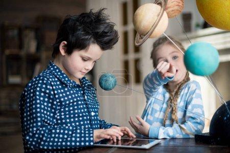 Photo pour Garçon à l'aide d'une tablette numérique tout en jeune fille pointant sur le modèle de système solaire - image libre de droit