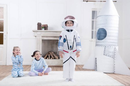 Photo for Girls looking on boy in astronaut costume at home - Royalty Free Image