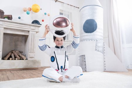 Photo for Boy in astronaut costume holding helmet, toy rocket behind - Royalty Free Image