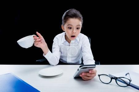 Photo pour Choqué petite fille femme d'affaires tenant tasse et en utilisant smartphone isolé sur noir - image libre de droit