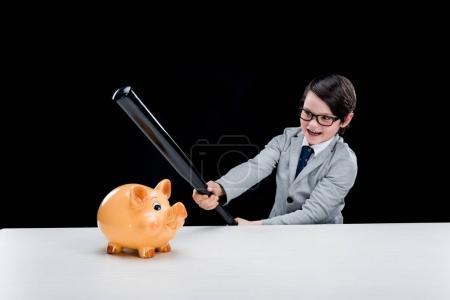 Photo pour Petit garçon en costume formel tenant batte de baseball frappant tirelire isolé sur noir - image libre de droit