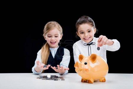 Photo pour Portrait de petites filles assises à table et calculant l'argent isolé sur noir - image libre de droit