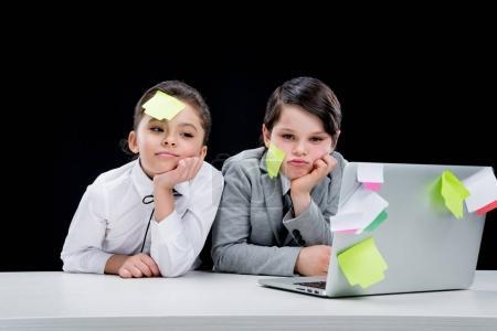 Photo pour Portrait de garçon et fille avec des notes sur les visages assis sur le lieu de travail isolé sur noir - image libre de droit