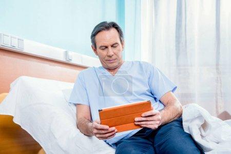 Photo pour Moyen patient âgé à l'aide de tablette numérique et assis sur le lit à l'hôpital - image libre de droit