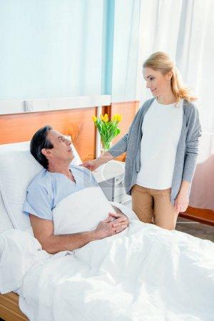 Photo pour Femme rendant visite à son mari d'âge moyen à l'hôpital - image libre de droit