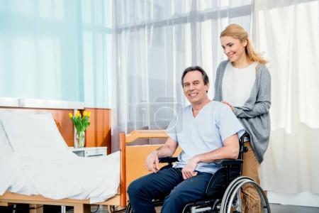Photo for Wheelchair man with wife near by in hospital chamber - Royalty Free Image