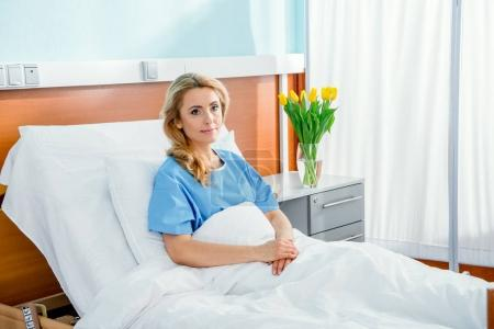 Photo for Pensive woman lying in hospital bed - Royalty Free Image