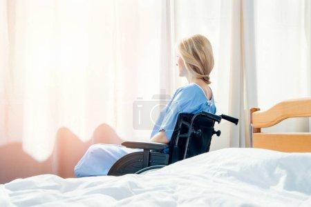 Foto de Vista lateral de la mujer de la silla de ruedas mirando a la ventana en el hospital - Imagen libre de derechos