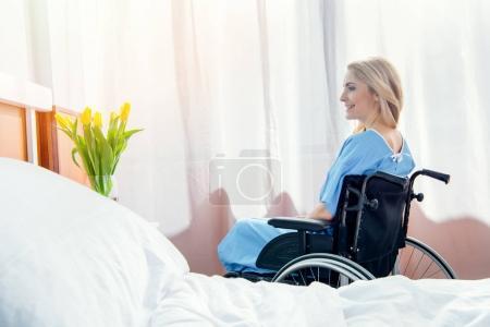 Foto de Vista lateral de la sonriente mujer de silla de ruedas mirando Tulipanes en hospital - Imagen libre de derechos