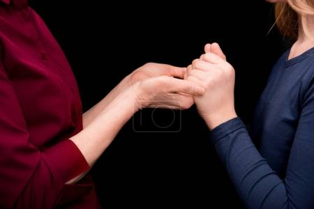 Photo for Cropped view of grandchild and grandmother holding hands isolated on black - Royalty Free Image