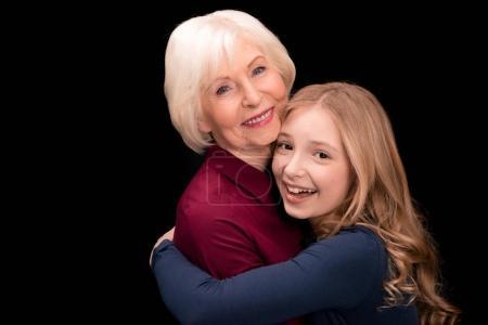 Photo pour Petit-enfant heureux et grand-mère hugging noir isolé en studio - image libre de droit