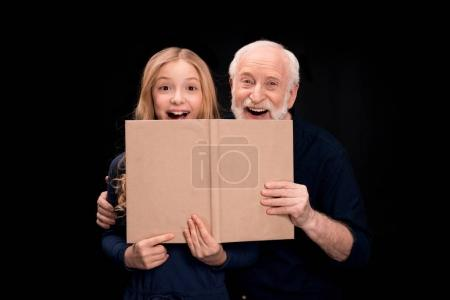 Grandfather and granddaughter holding book