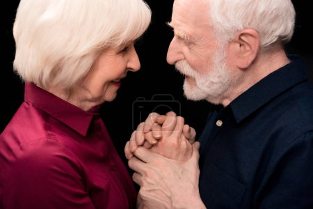 Photo for Senior couple smiling and holding hands isolated on black, senior couple happy concept - Royalty Free Image
