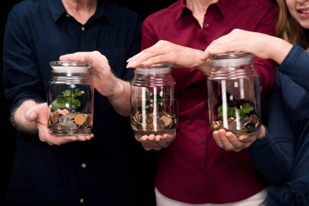 family holding jars with money