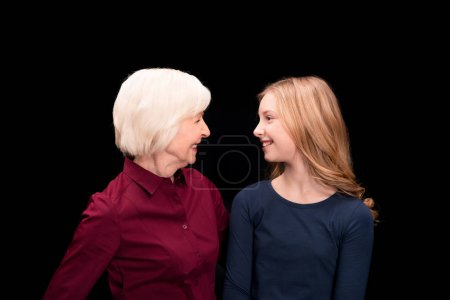 Photo pour Heureux petit-enfant et sa grand-mère en regardant l'autre isolé sur fond noir - image libre de droit