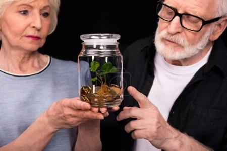 Photo for Close-up view of senior couple standing together and looking at coins and plant in glass jar - Royalty Free Image
