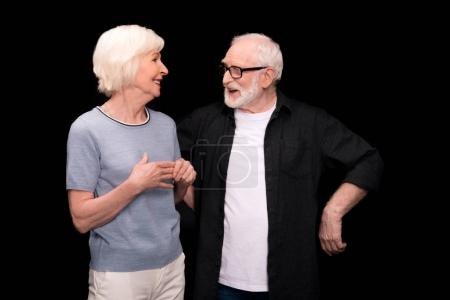 Photo for Happy senior couple standing together and talking isolated on black - Royalty Free Image