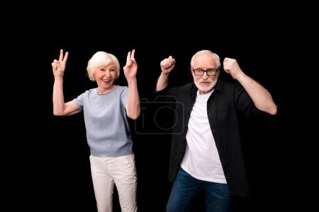 Photo for Happy active senior couple standing together and having fun isolated on black - Royalty Free Image