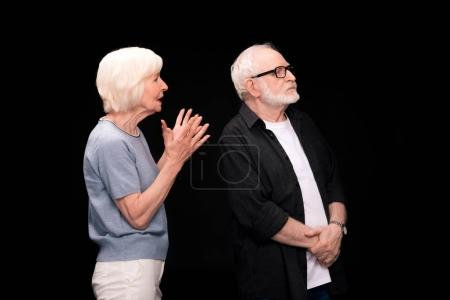 Photo for Serious senior couple standing and arguing isolated on black - Royalty Free Image