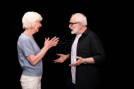 Photo for Side view of senior couple standing and gesturing isolated on black - Royalty Free Image
