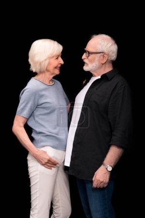 Photo for Side view of beautiful senior couple standing together and looking at each other isolated on black - Royalty Free Image