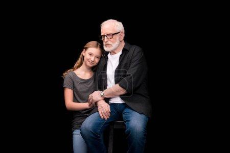Photo pour Petite fille souriante, s'appuyant sur l'épaule de grand-père isolée sur fond noir - image libre de droit