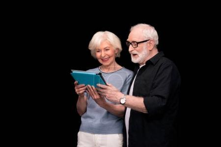 Photo pour Couple de personnes âgées souriant à l'aide de tablette numérique isolée sur fond noir - image libre de droit