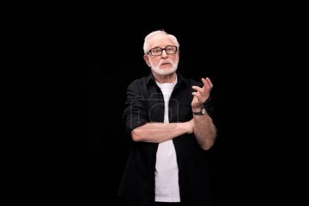 Photo pour Portrait d'un élégant homme senior réfléchie isolée sur fond noir - image libre de droit