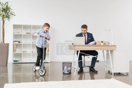 Boy riding skooter at office