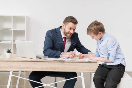 Businessman with son drawing on business papers