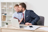 Businessman with his son in office