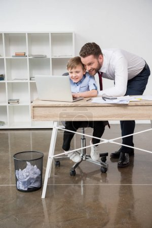 Businessman playing on laptop with son