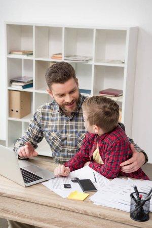 Photo pour Homme d'affaires pigiste travaillant à table avec son fils au bureau à domicile - image libre de droit