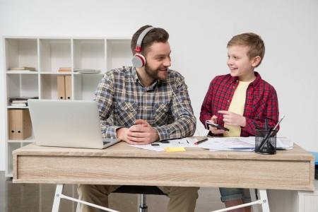 Businessman in headphones with son