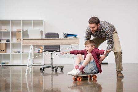 Businessman with son on skateboard