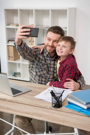 freelancer taking self portrait with son