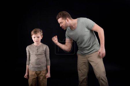 Foto de Padre enojado amenazando y gesticular a asustado poco hijo, problemas familiares concepto - Imagen libre de derechos