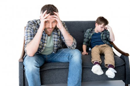 Photo for Upset father and son sitting on sofa after quarrel, family problems concept - Royalty Free Image