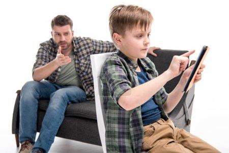 Photo pour Père parlant avec un petit fils assis sur une chaise et utilisant une tablette numérique, concept de problèmes familiaux - image libre de droit