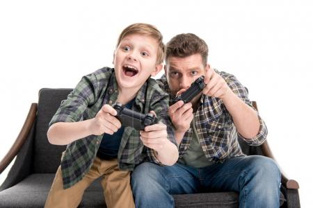 Photo for Father and son sitting on sofa and playing with joysticks isolated on white - Royalty Free Image