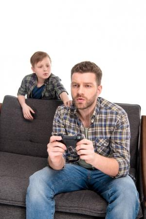 Photo for Little boy looking at father sitting on sofa and playing with joystick, family problems concept - Royalty Free Image