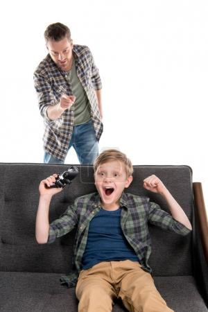 Photo for Serious father pointing with finger and excited son sitting on sofa with joystick, family problems concept - Royalty Free Image