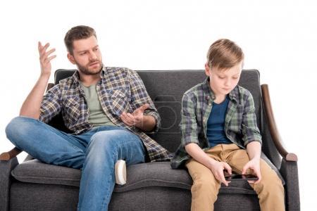 Photo pour Père gesticuler et parler au petit fils assis sur le canapé et en utilisant smartphone, concept de problèmes familiaux - image libre de droit