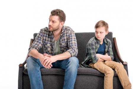Photo for Upset little boy with crossed arms and father sitting on sofa and looking away, family problems concept - Royalty Free Image