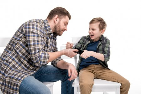 Photo for Father and emotional little son quarreling about smartphone, family problems concept - Royalty Free Image