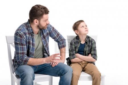 Foto de Padre hablando con el hijo pequeño sentado en silla con brazos cruzados y mirando hacia arriba, el concepto de problemas familiares - Imagen libre de derechos